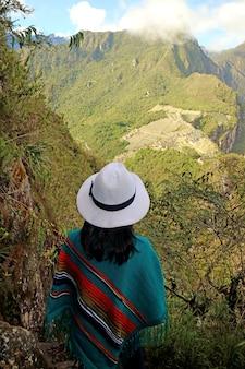 Vrouw onder de indruk van uitzicht op de ruïnes van de inca-citadel van machu picchu vanaf de berg huayna picchu, peru