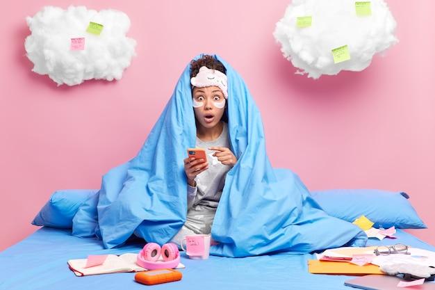 Vrouw onder deken wijst naar smartphone ontdekt schokkend nieuws brengt vrije tijd thuis door draagt slaapmasker en pyjama doet huiswerk in de verte
