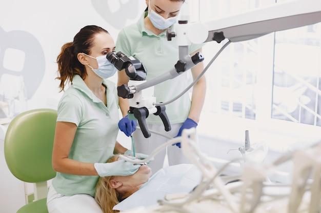 Vrouw onder tandheelkundige behandeling op het kantoor van de tandarts en vrouw wordt behandeld voor tanden.