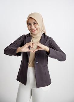 Vrouw ondernemer draagt hijab liefde teken hand pose, kantoor werk concept geïsoleerd