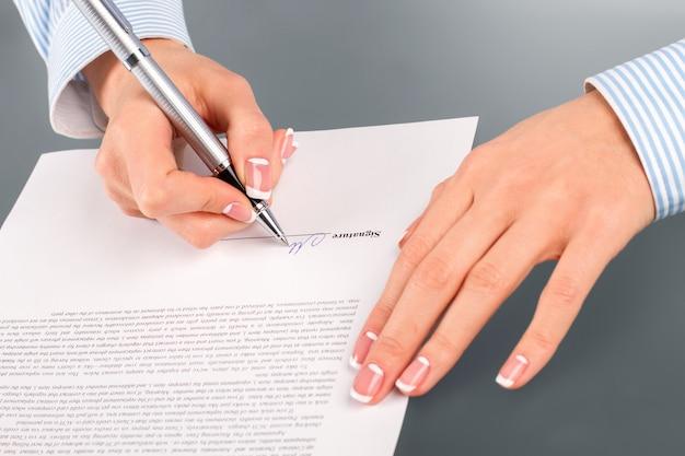 Vrouw ondertekening huurcontract. vrouwelijke werknemer tekent huurcontract. gunstig voor beide kanten. simpele duidelijke afspraak.