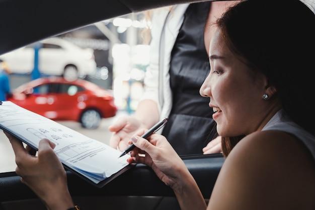 Vrouw ondertekent het document om de auto op te halen bij de autoverhuur.