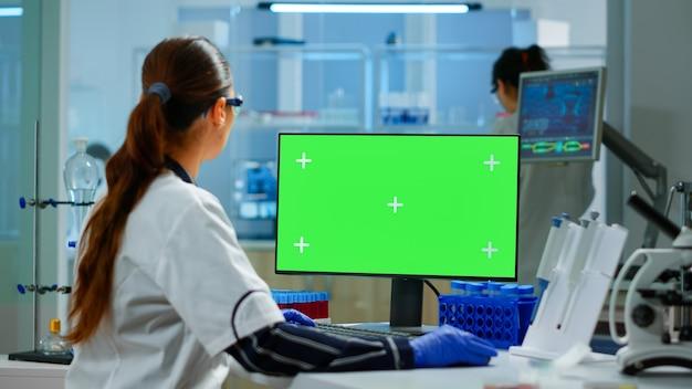 Vrouw onderzoeker typen op computer met groen scherm mockup display, sjabloon in toegepast wetenschappelijk laboratorium. ingenieur die experimenten op de achtergrond uitvoert en de evolutie van vaccins onderzoekt met behulp van hightech
