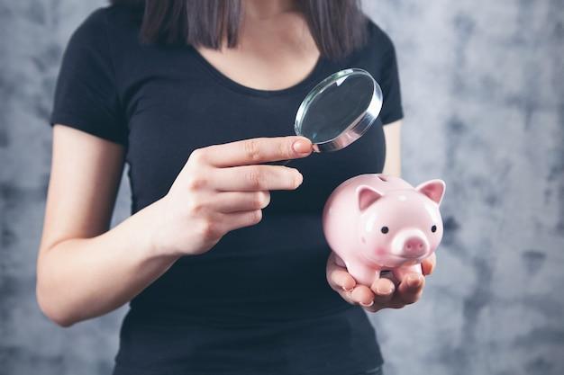 Vrouw onderzoekt een spaarvarken met een vergrootglas