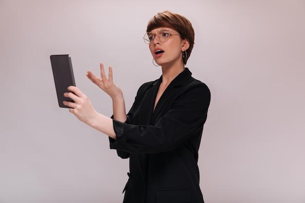 Vrouw onderzoekt tabletscherm met misverstand. zakelijke dame in zwarte jas vormt op geïsoleerde witte achtergrond