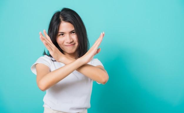 Vrouw ongelukkig of zelfverzekerd staande, ze houdt twee kruisende armen vast en zegt geen x-teken