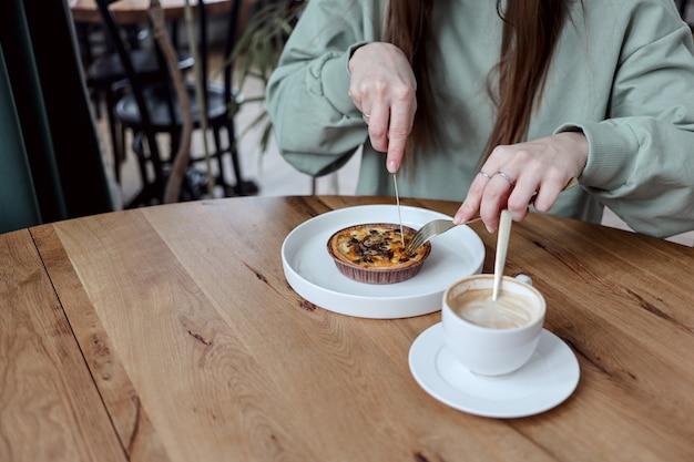 Vrouw ontbijt eten in een coffeeshop. een onherkenbare vrouw snijdt haar quiche met champignons om er koffie bij te eten. mensen en eten concept.
