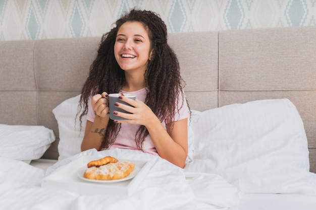 Vrouw ontbijten op bed in een licht hotelappartement of thuis. venster licht portret jong meisje croissant eten, koffie drinken en glimlachen.