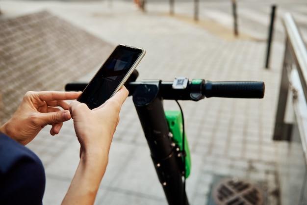 Vrouw ontgrendelt elektrische scooter te huur met een smartphone-applicatie