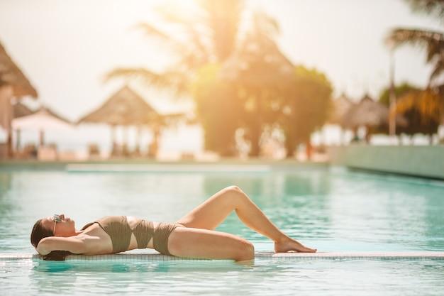 Vrouw ontspannen bij het zwembad in een luxe hotel resort genieten van perfecte strandvakantie vakantie