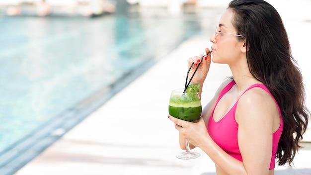 Vrouw ontspannen bij het zwembad met een drankje