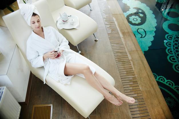 Vrouw ontspannen bij zwembad in badjas