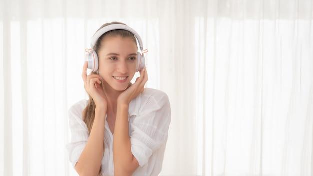 Vrouw ontspannen die aan muziek met hoofdtelefoons luistert.