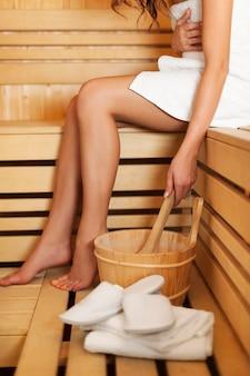 Vrouw ontspannen en sauna accessoires gebruiken