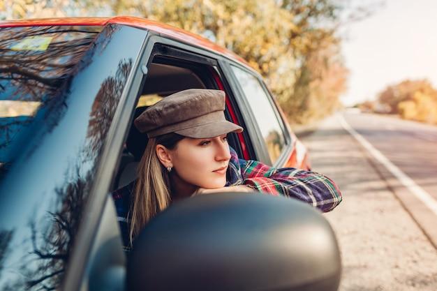 Vrouw ontspannen in auto. bestuurder die uit autimobiel venster op de herfstweg kijkt.