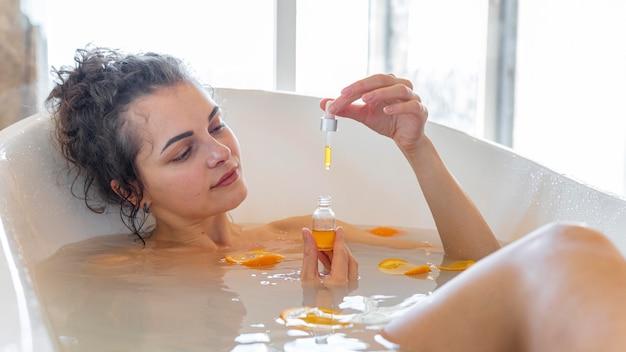 Vrouw ontspannen in bad met stukjes sinaasappel