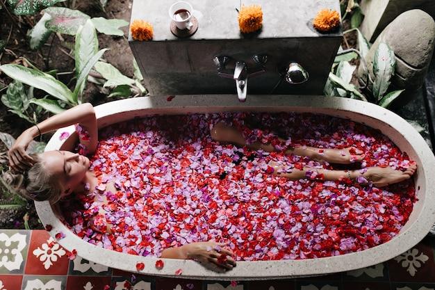 Vrouw ontspannen in bad. mooi blond vrouwelijk model dat van kuuroord met roze rozen geniet.