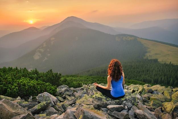 Vrouw ontspannen in de natuur op zonsondergang