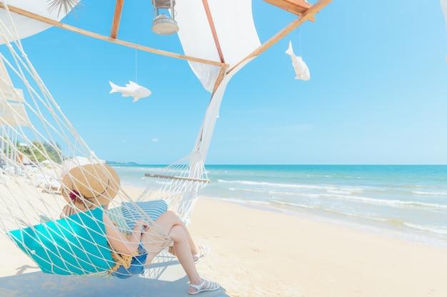 Vrouw ontspannen in een hangmat op het strand