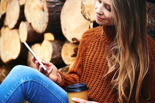 Vrouw ontspannen met koffiekopje en telefoon in herfstbos