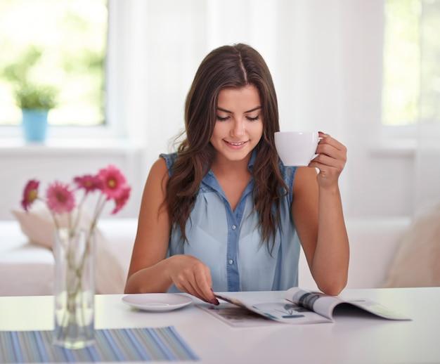 Vrouw ontspannen met krant en koffie
