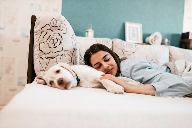 Vrouw ontspannen op bed met haar hond.