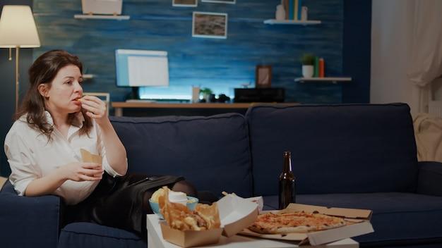 Vrouw ontspannen op de bank met afhaalmaaltijden thuis