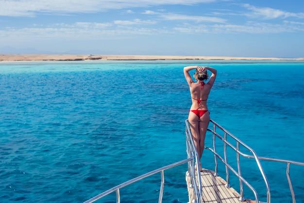 Vrouw ontspannen op de neus van het cruiseschip met open armen op zee