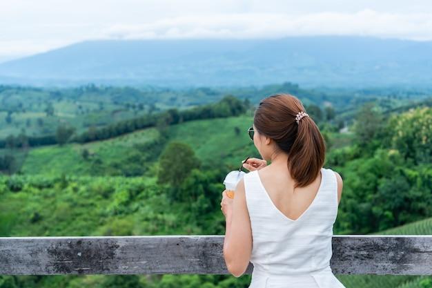 Vrouw ontspannen op de top van een berg en genieten van het uitzicht op de zonsondergang