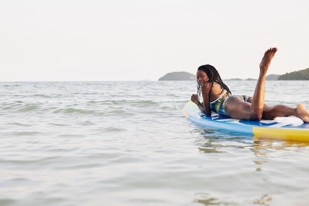 Vrouw ontspannen op drijvende sup board