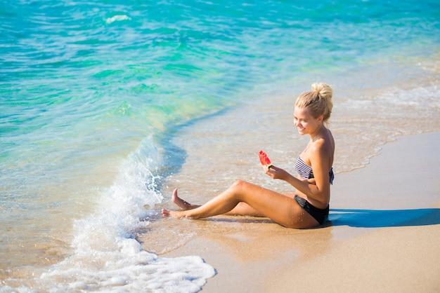 Vrouw ontspannen op het strand op een zomerse dag lachend met een plakje watermeloen in haar hand
