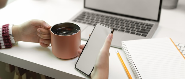 Vrouw ontspannen van het werk met mock-up smartphone en ijskoffie op witte tafel