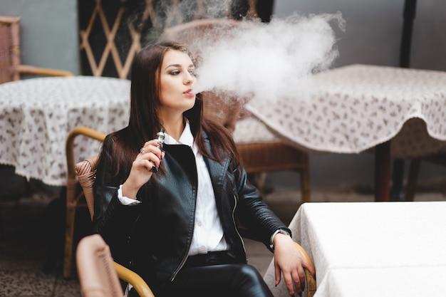 Vrouw ontspant roken vape en blaast dikke rook uit de mond.