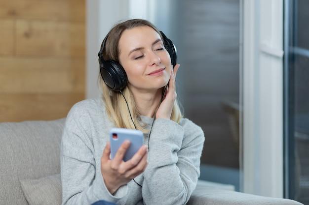 Vrouw ontspant thuis en luistert naar muziek met grote koptelefoon gebruikt mobiele telefoon