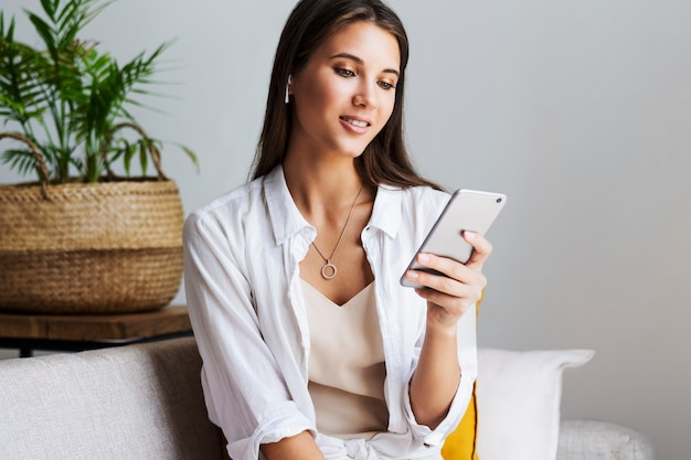 Vrouw ontspant thuis, gebruikt smartphone om te sms'en, foto's delen, communiceren met vrienden, e-mail controleren, video's bekijken, online games spelen. entertainmentmogelijkheden op met internet verbonden gadgets.