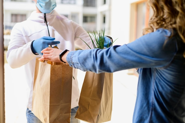 Vrouw ontvangen bestelde goederen van bezorger