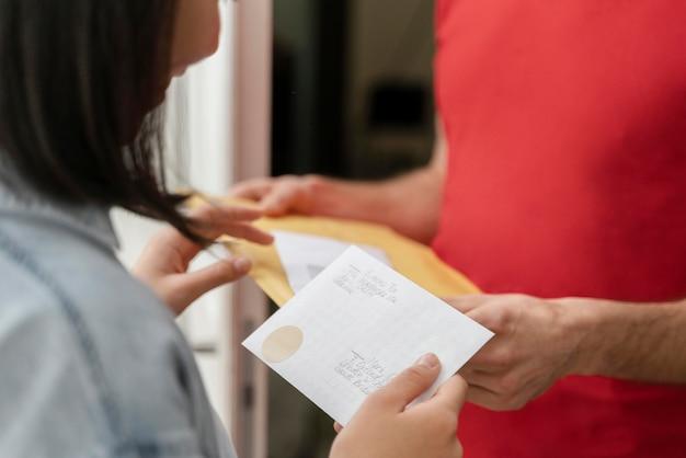 Vrouw ontvangen mail door bezorgdienst close-up