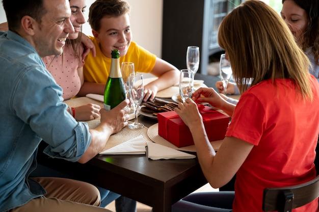 Vrouw ontvangt cadeau tijdens diner omringd door familie