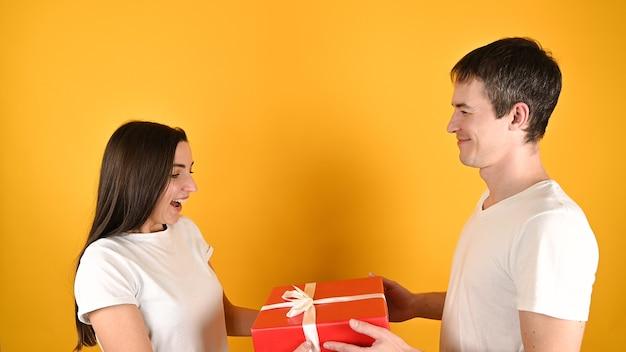 Vrouw ontvangt een geschenk van haar minnaar op geel