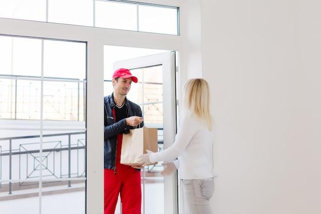 Vrouw ontvangt pakket van bezorger aan de deur.