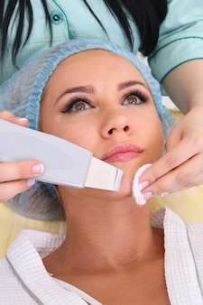 Vrouw ontvangt reinigingstherapie met een professionele ultrasone apparatuur in cosmetologie kantoor