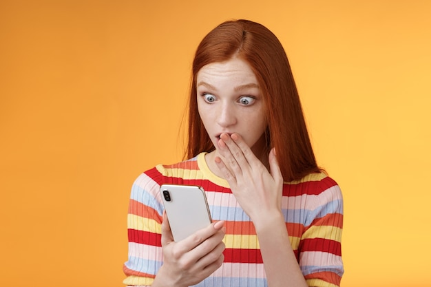 Vrouw ontvangt schokkend bericht naar adem snakkend naar mondpalm starend smartphonescherm ontdekte wie vriendje internet sociaal netwerk volgde en stond verbaasd opgewonden, oranje achtergrond.
