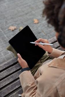 Vrouw ontwerper werkt aan digitale tablet downloads applicatie tekent met stylus poses buiten op houten bank