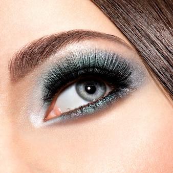 Vrouw oog met turquoise make-up. lange valse wimpers. macro-opname