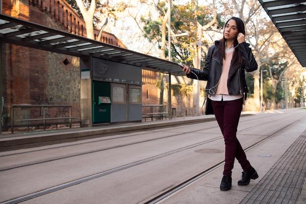 Vrouw oortelefoons zetten bij de halte van de tram