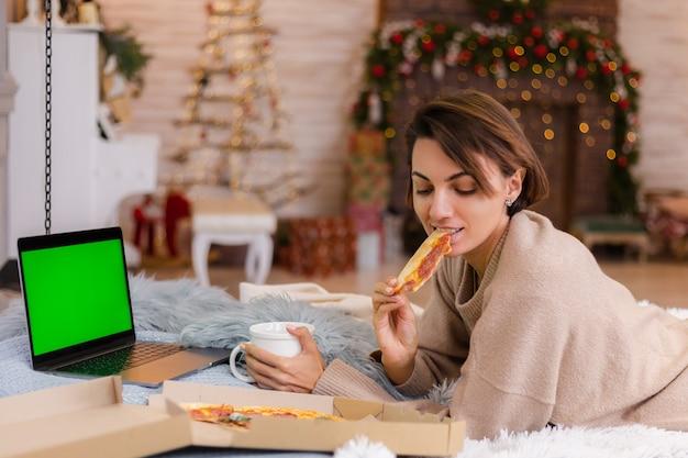Vrouw oosten fastfood pizza van levering op bed in de slaapkamer thuis met kerstmis nieuwjaar.