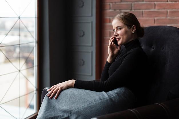 Vrouw op bank die bij telefoon spreekt