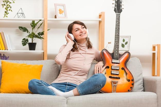 Vrouw op bank met gitaar