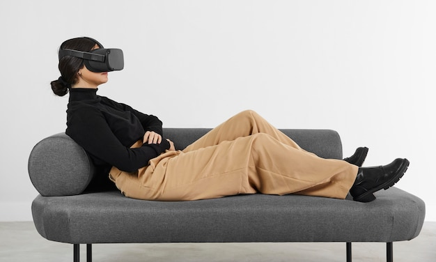 Vrouw op bank met virtual reality-headset Premium Foto