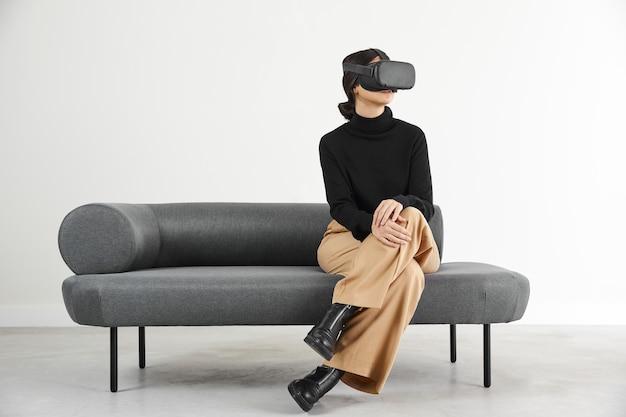 Vrouw op bank met virtual reality-headset Premium Foto